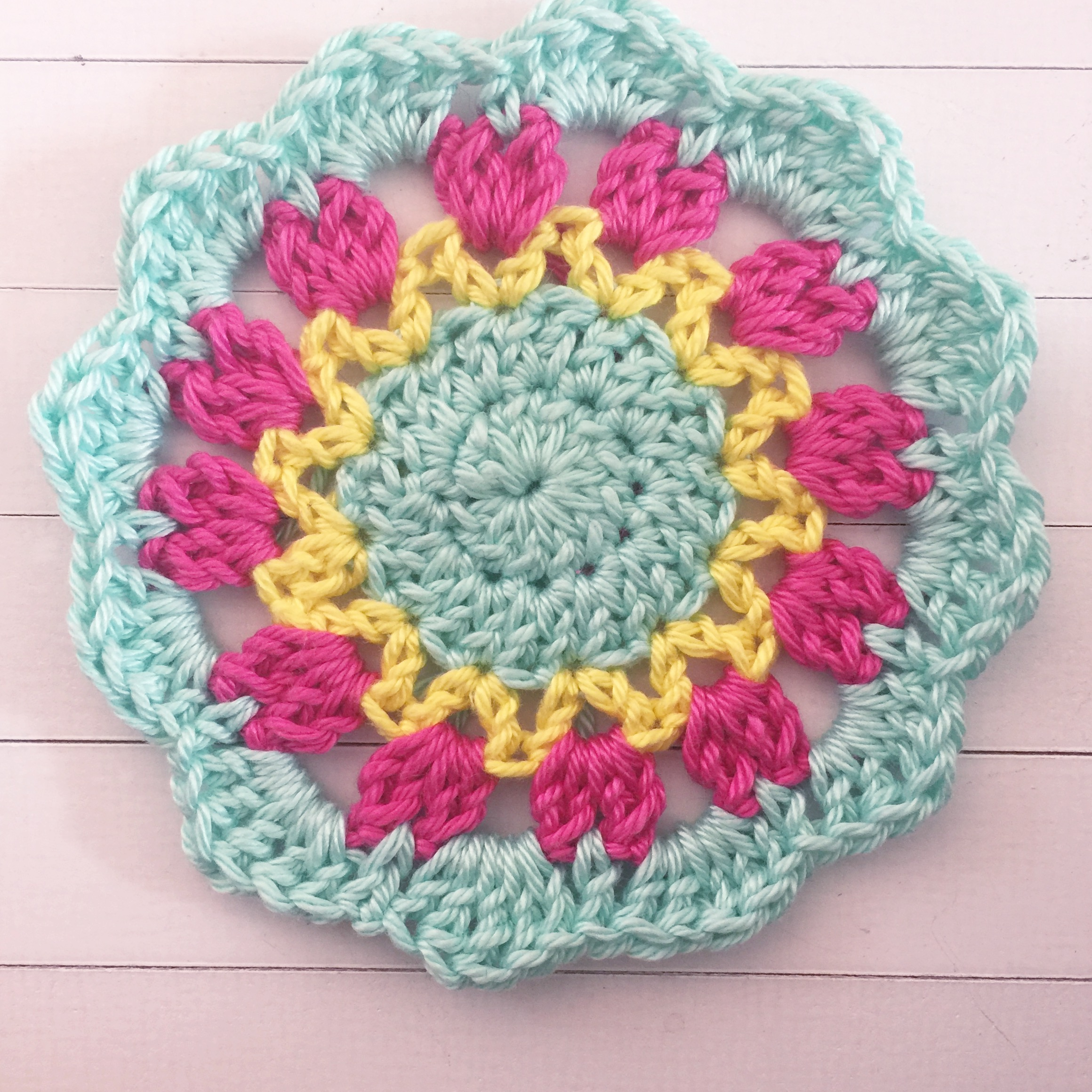 Join next colour to the middle loop of the cluster with a HDC (half double crochet). in the ch space, work a DC, Htr (half treble - YO twice, insert hook, pull up a loop, pull through two loops, YO, pull through all loops), a Tr (treble crochet), Htr and a DC. HDC into the top loop of the next cluster. Repeat this around in each ch space, slip stitch to join.