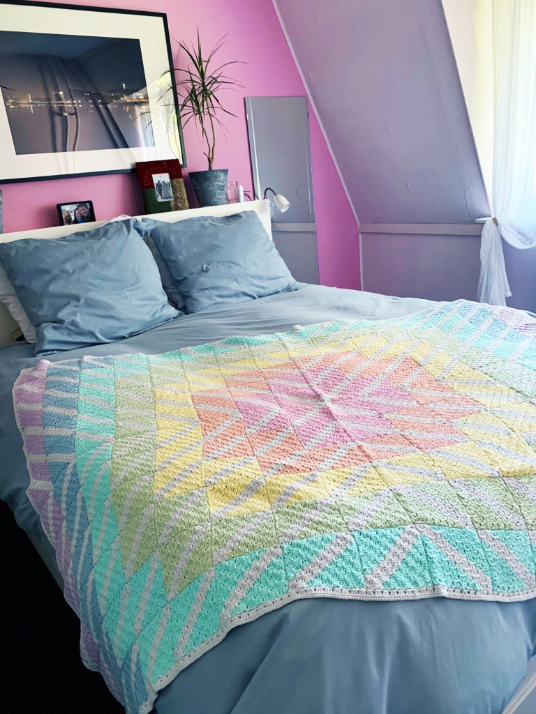 long shot of blanket draped over bed.  Purpose is to show the viewer how the blanket looks and to give an indication of size