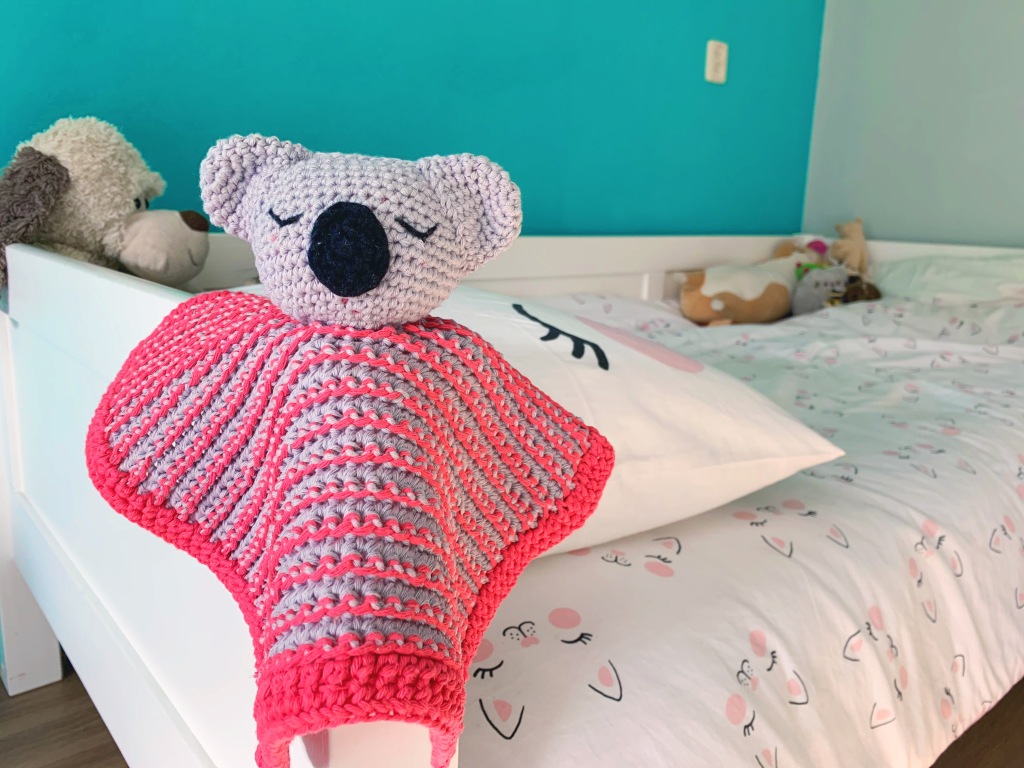 Koala lovey crochet toy lying on a bed